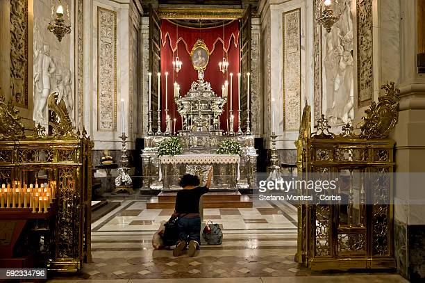 A woman prays in front of the chapel of Santa Rosalia where the remains of the patron saint of Palermo are kept inside the cathedral of the Blessed...