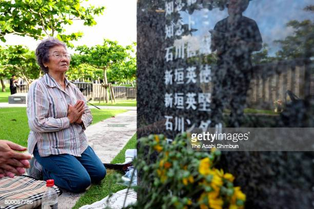 A woman prays in front of the Cornerstone of Peace where the names of their bereaved family members and relatives engraved at the Peace Memorial Park...