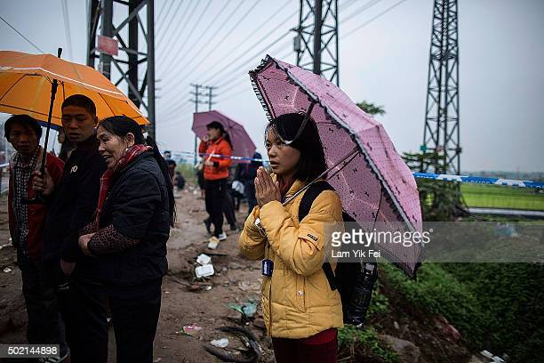 A woman prays near a collapse building after a landslide destroyed or damaged more than 30 buildings on December 21 2015 in Shenzhen China Reports...