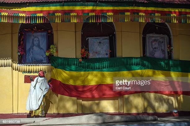 A woman prays next to a large Ethiopian flag and a picture of Christ outside a church as Timkat celebrations get under way on January 18 2017 in...