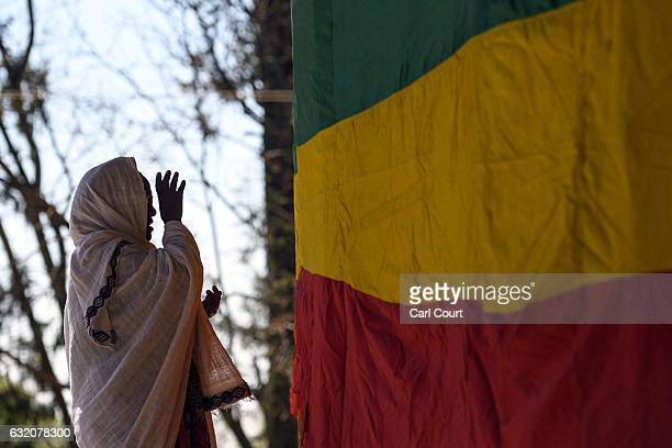 A woman prays next to a large Ethiopian flag outside a church as Timkat celebrations get under way on January 18 2017 in Gondar Ethiopia Timkat is...