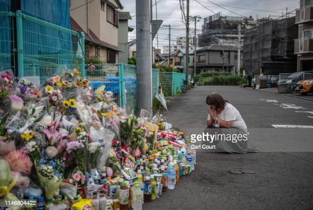 Woman prays next to flowers and tributes laid at the scene of a knife attack on a group of schoolchildren, on May 29, 2019 in Kawasaki, Japan. An...