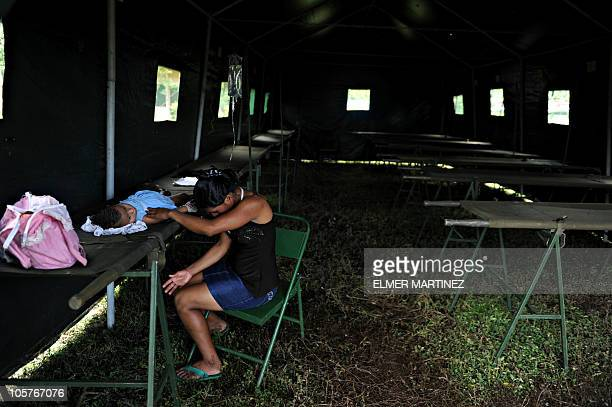 Woman prays next to her daughter with possible symptoms of the Leptospirosis virus in a field hospital in Achuapa, 220 km northwest of Managua, on...