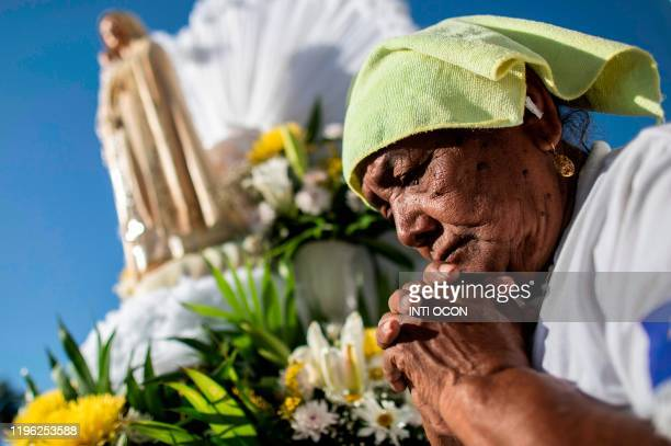 A woman prays next to the image of the Virgin of Fatima upon its arrival from Portugal to the Cathedral in Managua on January 25 2020