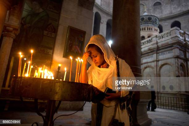 A woman prays next to The tomb of Jesus Christ with the rotunda is seen in the Church of the Holy Sepulchre on March 21 2017 in Jerusalem Israel The...