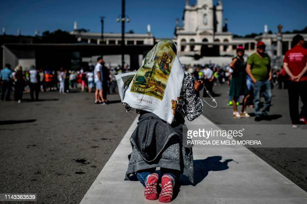 A woman prays on her knees at the Fatima shrine in Fatima central Portugal on May 12 2019 Thousands of pilgrims converged on the Fatima Sanctuary to...