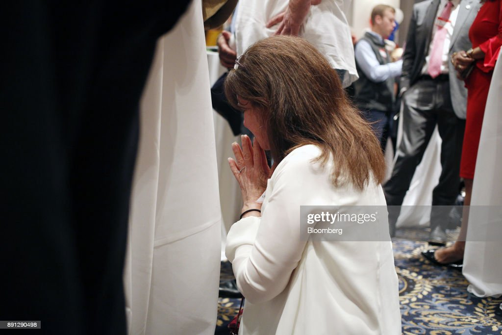 A woman prays on her knees during an election night party for Roy Moore, Republican candidate for U.S. Senate from Alabama, in Montgomery, Alabama, U.S., on Tuesday, Dec. 12, 2017. The defeat of Moore in Alabamas U.S. Senate race by Democrat Doug Jones was a stunning rebuke to the GOPs anti-establishment wing led by Steve Bannon and a major political embarrassment for President Donald Trump. Photographer: Luke Sharrett/Bloomberg via Getty Images