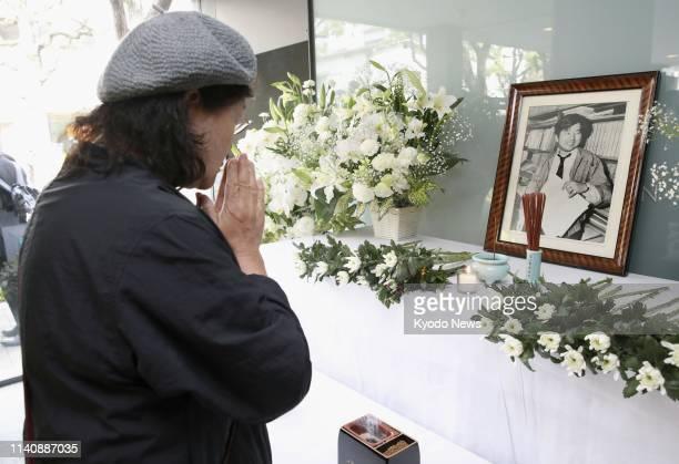 Woman prays on May 3 in front of an altar set up at The Asahi Shimbun's Nishinomiya bureau in western Japan for Tomohiro Kojiri, a reporter for the...