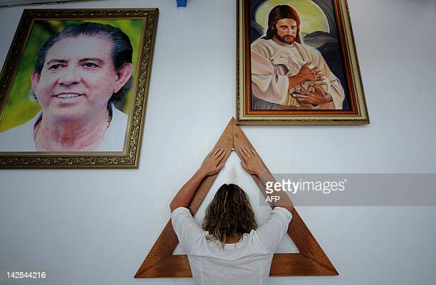 A woman prays on the Sacred Triangle of prayer which corners represent faith love and charity at John of God's 'Casa de Dom Inacio de Loyola' in...