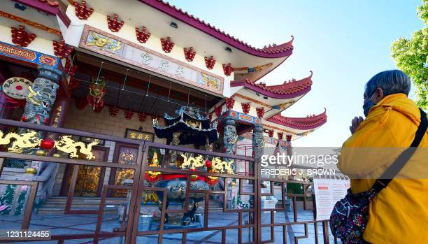 Woman prays outside the Thien Hau Temple, closed due to the coronavirus pandemic, on the first day of the Lunar New Year of the Ox in the Chinatown...