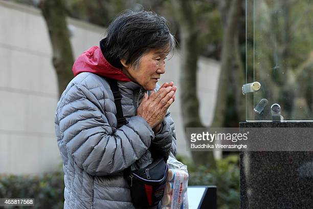 A woman prays over the lighted bamboo candles placed in the shape of the date 311 to commemorate the victims of Great East Japan Earthquake and...