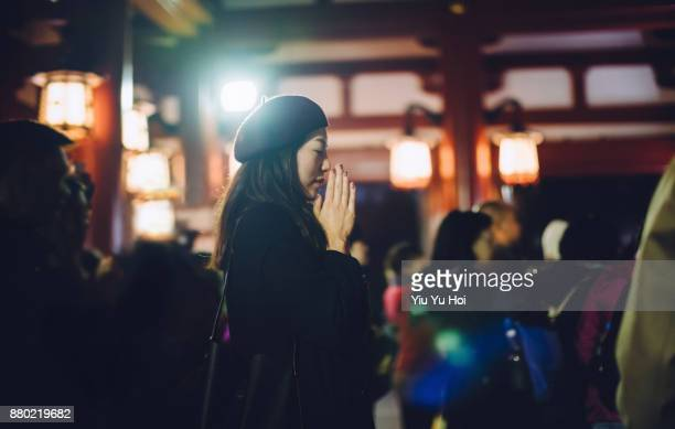 woman prays sincerely in a japanese temple - sincerely yours ストックフォトと画像