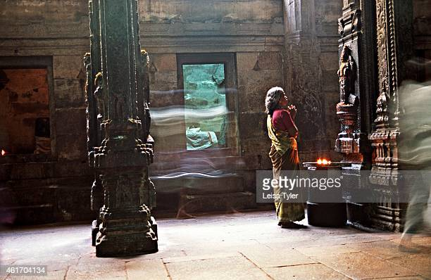 A woman prays to a Hindu God in the vast temple complex of Madurai Tamil Nadu Dedicated to the Hindu Goddess Meenakshi the temple is believed to be...