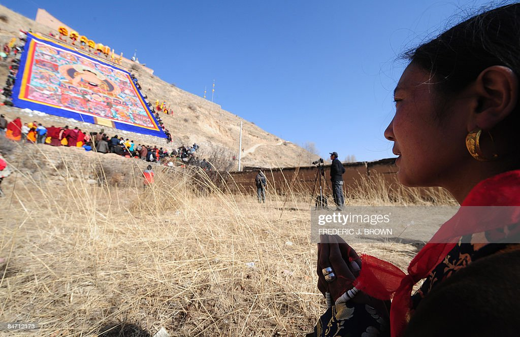 A woman prays while facing a momentarily : News Photo
