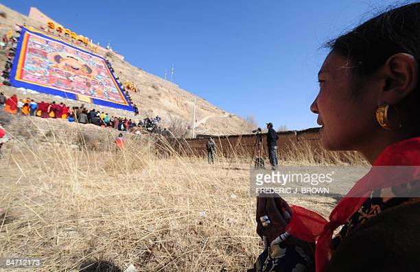 A woman prays while facing a momentarily unfurled Tibetan Buddhist thangka during the Sunning of the Buddha when a huge silk thangka of Sakyamuni the...