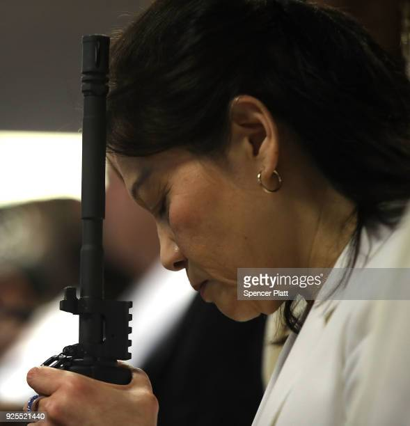 A woman prays while holding an AR15 rifle during a ceremony at the World Peace and Unification Sanctuary in Newfoundland Pennsylvania on February 28...