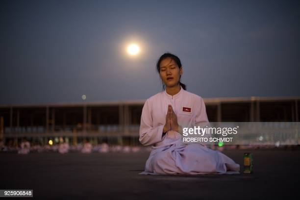 A woman prays while the full moon rises behind her during Makha Bucha Day celebrations at Wat Phra Dhammakaya temple near Bangkok on March 1 2018...