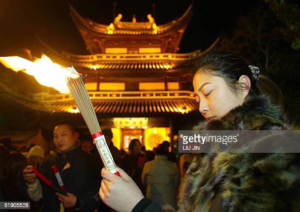 A woman prays with burning incense during New Year's celebrations at Longhua Temple in Shanghai 01 January 2005 For Chinese when the new year comes...