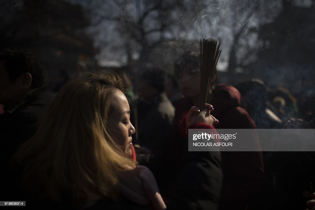A woman prays with incense sticks to celebrate the Lunar New Year, marking the Year of the Dog, at the Lama temple in Beijing on February 16, 2018. The Lunar New Year fell on February 16 this year, with celebrations in China scheduled to last for a week. /