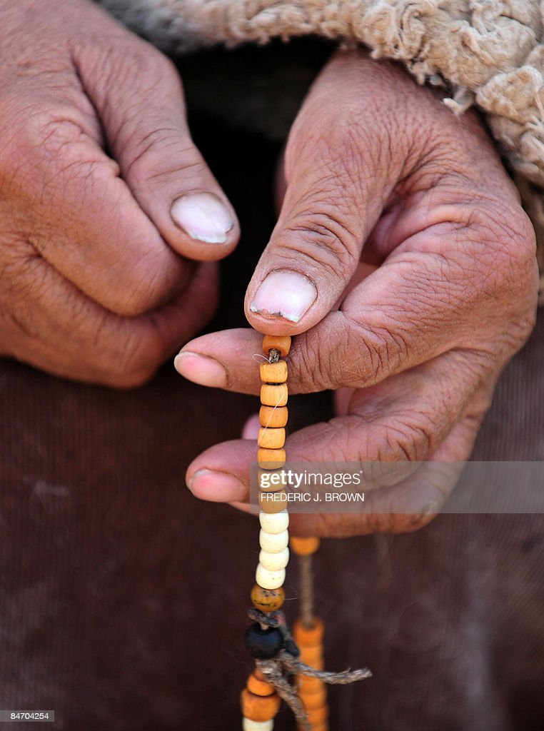 A woman prays with prayer beads at the N : News Photo
