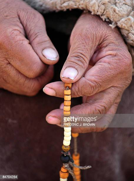 A woman prays with prayer beads at the Nyentog Monastery also known as Nianduhu during celebrations for the ongoing Monlam or Great Prayer Festival...