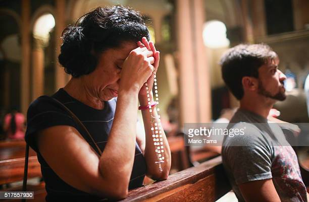 A woman prays with rosary beads in the Nossa Senhora da Paz church following a Good Friday procession during Semana Santa festivities on March 25...