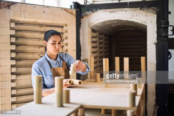 woman prepare kiln in pottery factory. - pottery stock pictures, royalty-free photos & images