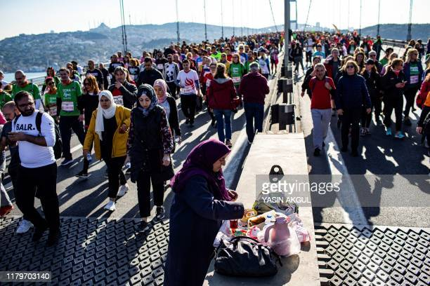 A woman prepares a breakfast among runners crossing the July 15 Martyrs' Bridge known as the Bosphorus Bridge during the 41st annual Istanbul...