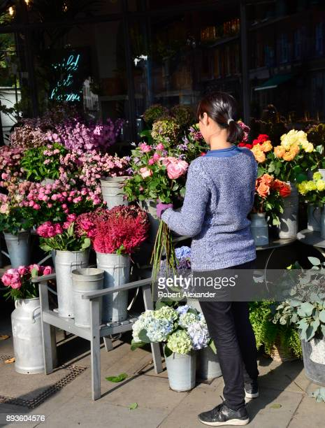 A woman prepares a bunch of roses for display at a flower shop in London England