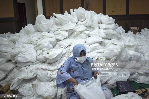 TOPSHOT A woman prepares basic need packages to distribute to people affected by the COVID19 coronavirus in Surabaya on April 26 2020