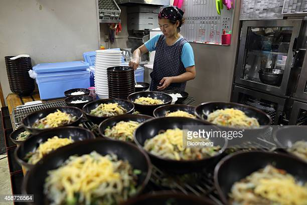 A woman prepares bowls of bibimbap a Korean rice dish in a canteen at the Korean High School in Tokyo Japan on Thursday Sept 25 2014 The school in...