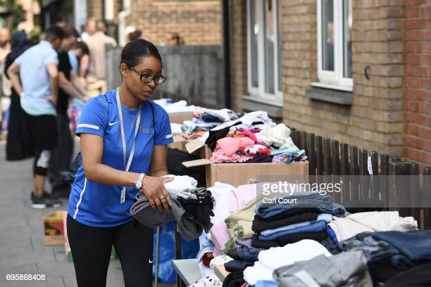 A woman prepares clothes at a stall which has been set up to help people near the burning 24 storey residential Grenfell Tower block in Latimer Road...