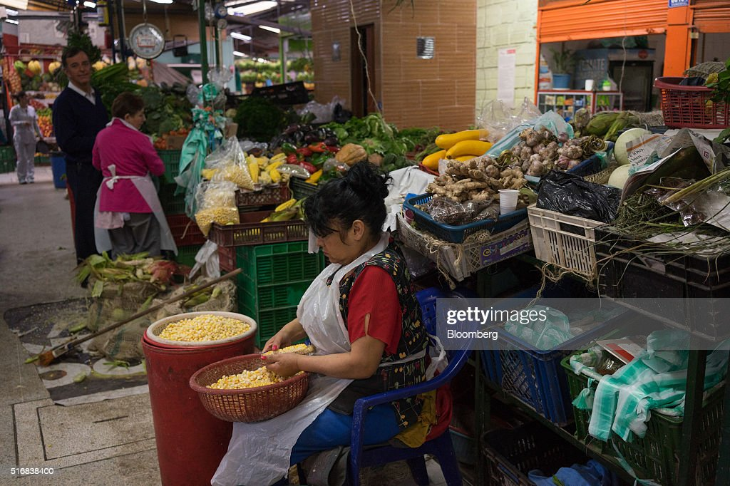 A woman prepares corn for sale at the Paloquemao market in Bogota, Colombia, on Wednesday, March 16, 2016. Colombia's central bank raised its benchmark interest rate for a seventh straight month as the inflation outlook continued to worsen and economic growth unexpectedly accelerated. Photographer: Mariana Greif Etchebehere/Bloomberg via Getty Images