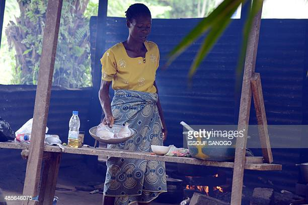 A woman prepares fish at a 'maquis' a small African restaurant in Kobakro outside Abidjan which now serves various types of meat instead of bushmeat...