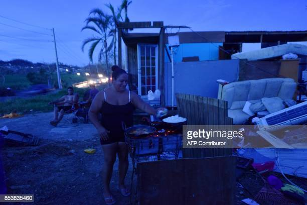 A woman prepares food during nightfall outside her house destroyed by Hurricane Maria in Toa Altaa Puerto Rico on September 25 2017 The US island...