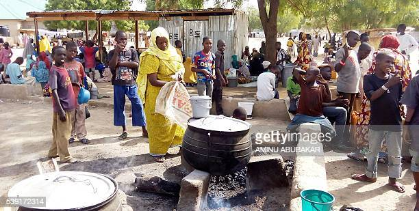 A woman prepares food for lunch in an openair kitchen for people displaced by Boko Haram violence on May 19 2016 in the Dalori Internally Displaced...