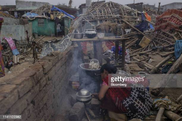A woman prepares food inside a damaged home after Cyclone Fani passed through Puri Odisha India on Saturday May 4 2019 A category 4 storm with strong...