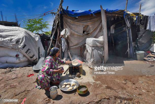 A woman prepares food outside a makeshift home on day ten of the 21day nationwide lockdown to curb the spread of coronavirus at Okhla on April 3 2020...