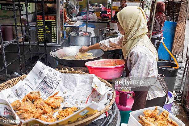Woman prepares fried fish at a restaurant in Kuala Lumpur, Malaysia, on Tuesday, March 18, 2014. Malaysia, aspiring to become a developed nation in...