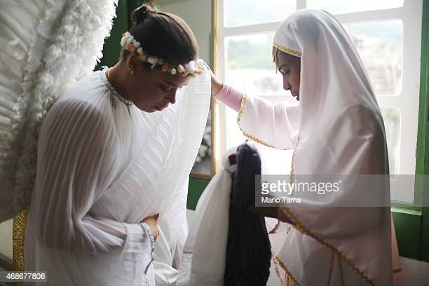 A woman prepares her angel outfit for the annual Easter procession during traditional Semana Santa festivities on April 5 2015 in Ouro Preto Brazil...