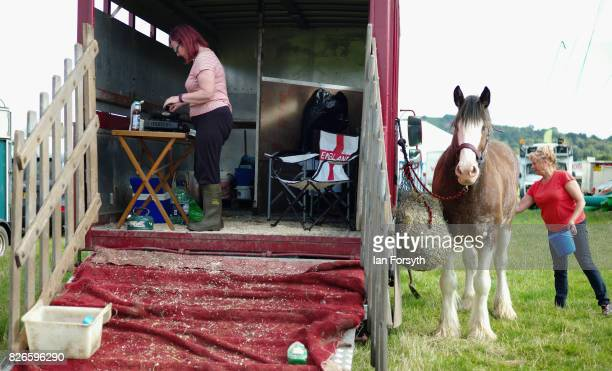 Woman prepares her horse while her friend cooks bacon sandwiches in the back of their horsebox during the Osmotherley Country Show on August 5, 2017...