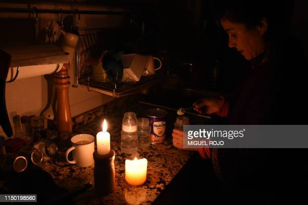 TOPSHOT A woman prepares milk bottles using candles at her home in Montevideo on June 16 2019 during a power cut A massive outage blacked out...