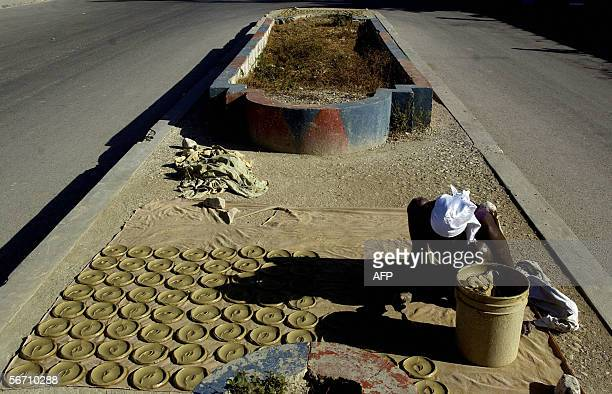 A woman prepares mud cakes on a street in the CiteSoleil slum of the Haitian capital PortauPrince 31 January 2006 Former president and frontrunner in...