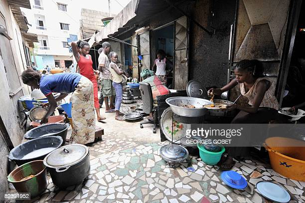 A woman prepares rice and fish on August 17 2008 at her street restaurant in Dakar where more and more residents can only afford some beans or bread...