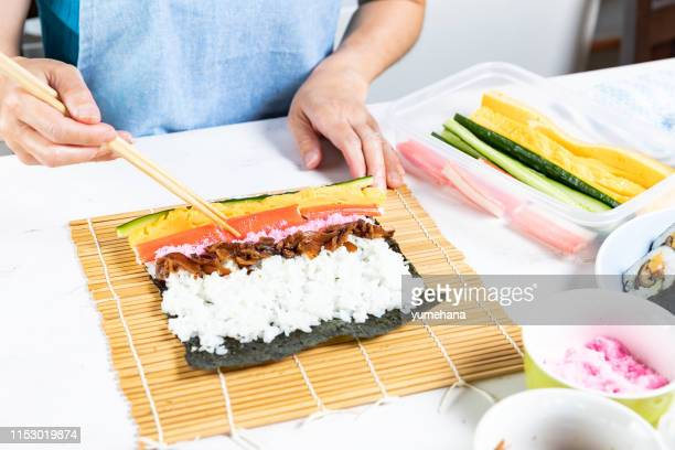 woman prepares sushi rolls, hands closeup - maki sushi stock pictures, royalty-free photos & images