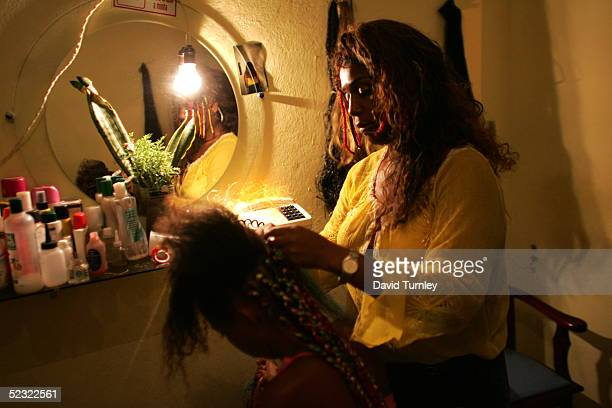 A woman prepares the hair of a young woman before joining in a parade in the streets of Salvador Brazil during the Carnival on February 5 Centuries...