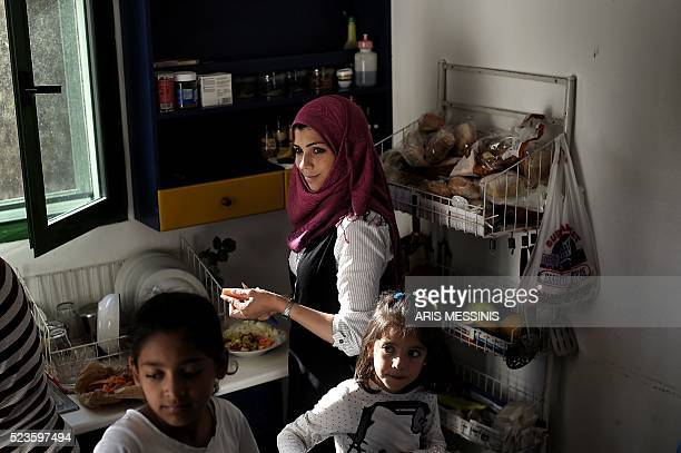 A woman prepares the lunch for her families in the kitchen of their apartment in a summer resort in Myrsini sheltering nearly 350 Syrian refugees...