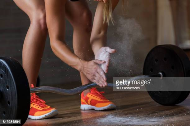 Woman prepares to deadlift  with barbell