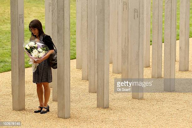 A woman prepares to lay a bouquet of flowers at the memorial to the victims of the July 7 2005 London bombings in Hyde Park on July 7 2010 in London...