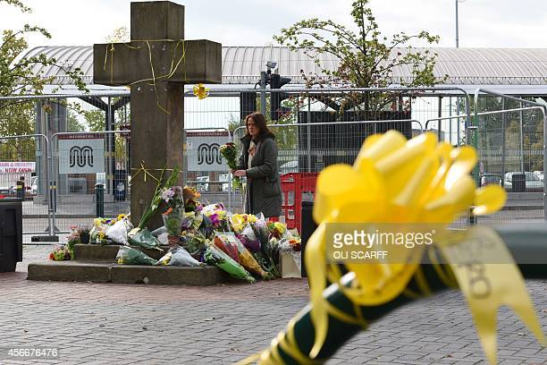 A woman prepares to place a floral tribute at the base of the Eccles Cross for murdered aid worker Alan Henning in Eccles north west England on...